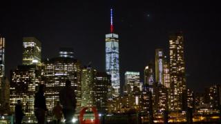 The One World Trade Center spire is lit blue, white and red after New York Gov. Andrew Cuomo announced the lighting in honor of dozens killed in the Paris attacks Friday