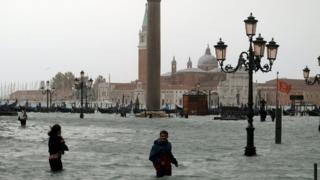 People walk in flooded St Mark Square in Venice on 29 October 2018