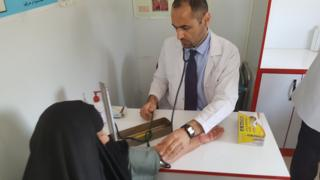 Dr Laith Al-Rubaiy assessing a patient in Iraq