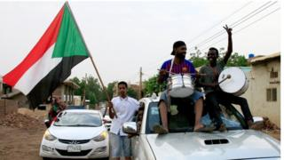 "Sudanese demonstraters wave their national flag as they celebrate in Khartoum early on August 3, 2019, after Sudan""s ruling generals and protest leaders reached a ""full agreement"" on the constitutional declaration."