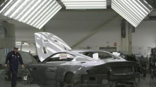 A man works on an Aston Martin