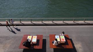 Corredores se exercitam na margem do Sena enquanto outras pessoas lem livros em mesas de piquenique