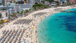 Tourist sunbathe at Magaluf beach