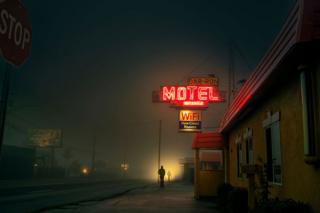 A view of a misty street at night with neon motel sign