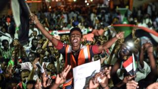 Sudanese protesters wave flags and flash victory signs as they gather for a sit-in outside the military headquarters in Khartoum on May 19, 2019. - Talks between Sudan's ruling military council and protesters are set to resume, army rulers announced, as Islamic movements rallied for the inclusion of sharia in the country's roadmap. (