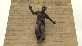 The bronze statue shows Jesus Christ wearing jeans and a shirt