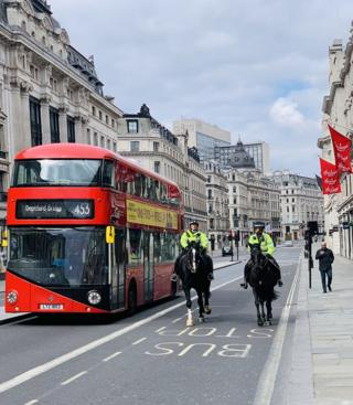 Mounted police and a London bus