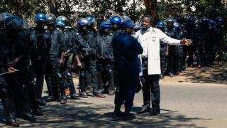 "A doctor speaks with the anti-riot police for a safe passage during a protest of doctors and medical staff for the safe return of Dr Peter Magombeyi, the leader of the Zimbabwe Hospital Doctors Association (ZHDA,) on September 18, 2019, in Harare. - Hundreds of Zimbabwean doctors and nurses marched in Harare on September 16, 2019, to protest the suspected kidnapping of a doctors' union leader by security forces for organising a slew of strikes. Peter Magombeyi has been missing since September 14, 2019, night, after sending a WhatsApp message saying he had been ""kidnapped by three men"", according to the Zimbabwe Hospital Doctors Association (ZHDA)."