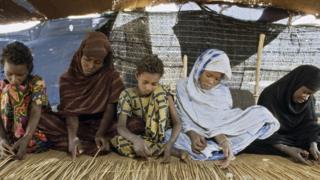 UN photo of girls making a carpet