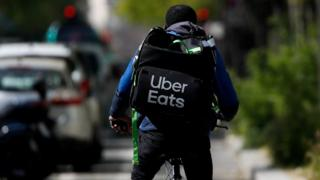 A deliveryman for Uber Eats rides a bike in Paris during a lockdown imposed to slow the spread of the coronavirus disease (COVID-19) in France, France, April, 1, 2020.