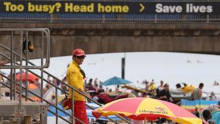 An RNLI Lifeguard patrols Boscombe beach in Dorset