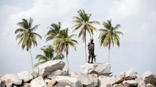 A policeman stands guard atop rocks overlooking the proposed Dangote oil refinery site during a facility tour near Akodo beach in the outskirt of Nigeria's commercial capital Lagos June 25, 2016.