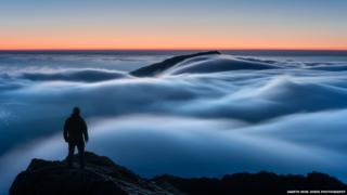A man stands, his back to the camera, on a mountain peak. Thick cloud covers the landscape at dawn