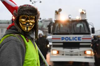 Ein Demonstrant steht vor einem Polizeifahrzeug in Paris.