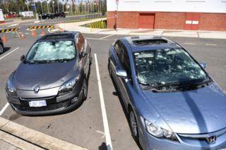 Damaged cars are seen parked outside Old Parliament House after a hail storm hit Canberra