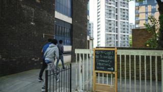 3 boys walking on housing estate near sign reading no to guns! no to knives!