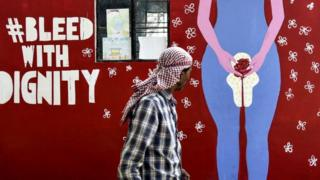 An Indian man looks on as he walks along a wall painting about menstruation in Guwahati on May 28, 2019