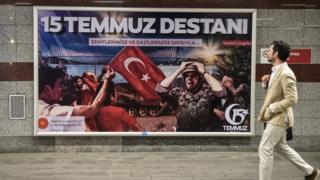 seorang pria berjalan melewati billboard dengan gambar tentara, bendera Turki, dan tulisan 15 Temmuz Destani