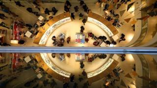 Customers are reflected as they shop in a John Lewis department store