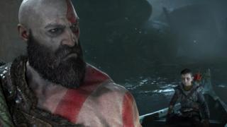 Kratos looks back over his shoulder at his son, sat in a boat behind him.