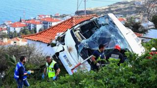 Bomberos de pie cerca de los restos del autobús de turistas que se salió de la carretera en Madeira el 17 de abril de 2019
