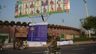 Pakistani policemen ride past a billboard featuring International World XI cricketers displaying outside the Gaddafi Cricket Stadium in Lahore on 10 September 2017