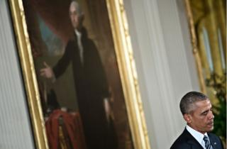 President Obama standing before a portrait of George Washington