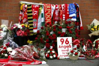 Flowers are placed at the Hillsborough memorial plaque during the Hillsborough 27th Anniversary Memorial Service at Anfield