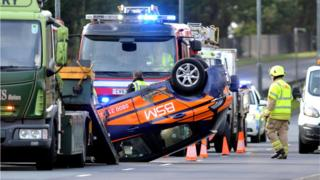Emergency services at crash scene with one car on its roof