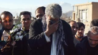 Mourners attend the burial of the victims of a suicide bomb attack in Kabul (21 January 2016)