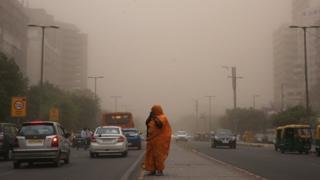 Una mujer camina con su rostro cubierto en medio de una tormenta de polvo y arena en Nueva Delhi, India.