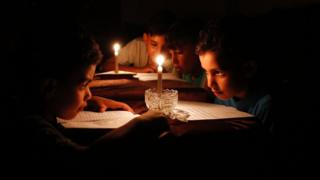 Palestinian children at home reading books by candle light because of electricity shortages in Gaza City.