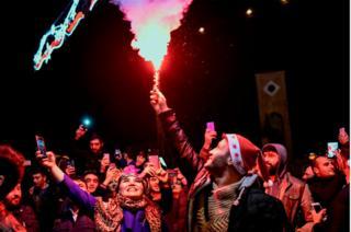 Un grupo de personas celebran con fuegos artificiales y luces de sus celulares en Estambul.