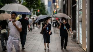 People wearing face masks shelter from the rain under umbrellas as they walk along a street on 30 June, 2020 in Tokyo, Japan.