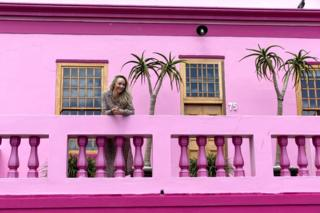A tourist looks out from a balcony of a home in the Bo-Kaap neighborhood in Cape Town, South Africa, 30 October 2019. The Bo-Kaap Civic and Ratepayers Association has been awarded a gold certificate at the 2019 Simon van der Stel Awards for its efforts to preserve the heritage of their area. A one billion Rand development on the fringes of the Bo-Kaap was halted by residents in a clash with police in November last year. The Bo-Kaap neighborhood on Signal Hill dates back to the establishment of a Dutch colony on the Cape of Good Hope in the seventeenth century. It is a multi-ethnic and multi-lingual community composed of descendants from South and Southeast Asian nations who had been forcibly relocated to supply skilled labor for the expanding Cape Colony. The Bo-Kaap is recognized globally for its distinctive vernacular architecture and its enduring Muslim culture. The district preserves the largest collection of pre 1850 architecture in South Africa including the countries oldest mosq
