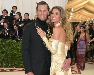 NFL quarterback Tom Brady and his wife, Gisele Bündchen, appear on the red carpet.