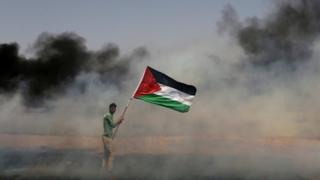 A demonstrator holds a Palestinian flag during clashes in the Gaza Strip in 2018