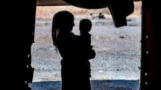 kampta bir kadının kucağında bir bebek