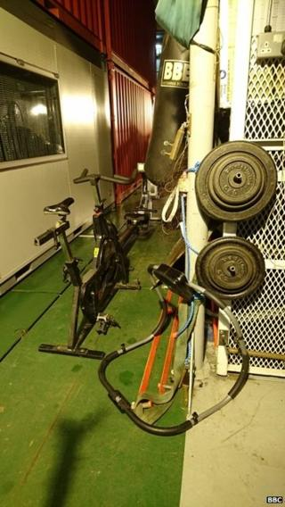 Picture of a black exercise bike and weights in the foreground.