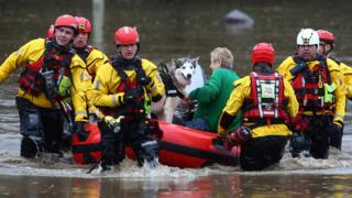 Members of the emergency services evacuate residents and their dogs from flooded houses