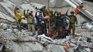 Rescatistas alzan sus puños como una señal para pedir silencio y poder captar el sonido de algún sobreviviente atrapado entre los escombros tras el terremoto en México.