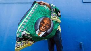 Un militant du parti au pouvoir exhibe un tissu avec la photo du président Ramaphosa.