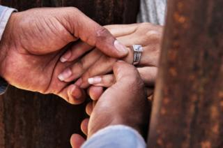 Rogelio gives Miriam her wedding ring as they get married through the border wall between Mexico and the United States