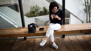 woman checking phone sitting on a bench, wearing sneakers