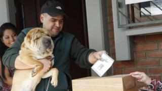 This handout picture shows Bolivian a citizen with his dog casting his vote in the ballot box on 21 February, 2016 in La Paz, Bolivia