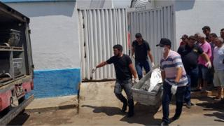 Forensic experts carry a corpse to be transported to the morgue after an attempted bank robbery in Milagres, Ceara state, Brazil, December 7, 2018