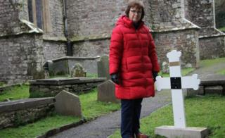 Janet Bradshaw by the grave of Leonie Demoulin at Laugharne