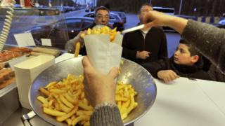 A woman serves Belgian fries to customers at a chips stand, in Brussels.