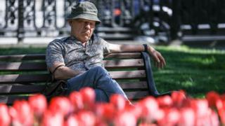 A man sits on a bench looking sad.