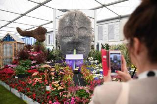 A visitor photographs a display by Baroness Floella Benjamin, called Floella's Future